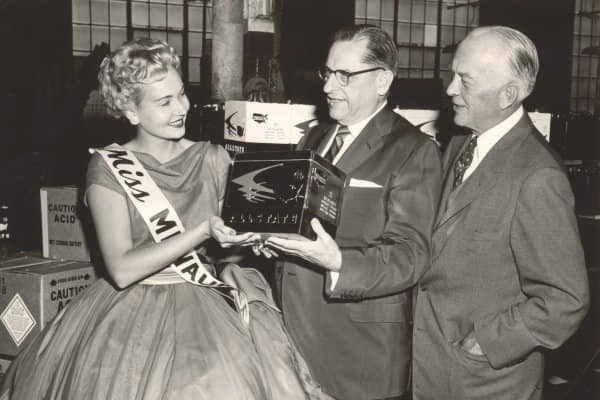 On September 5, 1958, Globe-Union, Inc. (predecessor to today's Power Solutions Group) produced its fifty-millionth battery for Sears, Roebuck & Co.  From left to right, Miss Milwaukee 1958 (Carmen Shields), Sears president Charles H. Kellstadt and Globe-Union president C. O. Wanvig, Sr. admire the fifty-millionth battery.