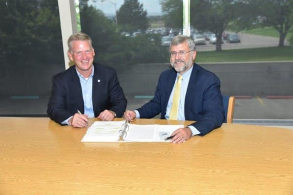 Chris Schulken, Regional Vice President Energy Solutions at Johnson Controls, and Karl Spieker, Vice President at CSU-Pueblo sign $12.5 million Performance Infrastructure contract.