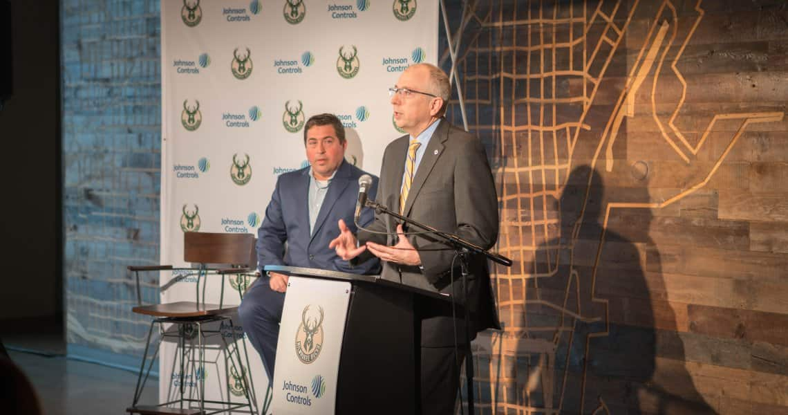 "Johnson Controls Chairman and CEO Alex Molinaroli discusses the company's partnership with the Milwaukee Bucks as Bucks President Peter Feigin watches. Johnson Controls is the official ""smart building"" partner for the new Wisconsin Entertainment & Sports Center in downtown Milwaukee."