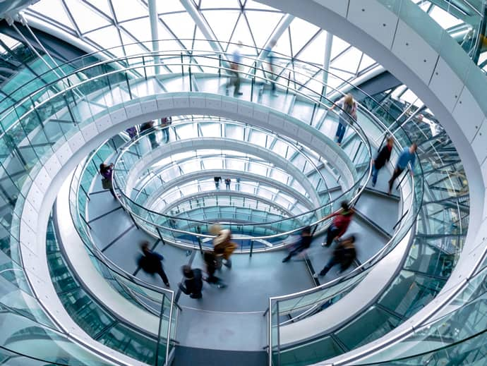 people walking on glass spiral staircase