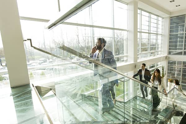 office staff climbing glass staircase