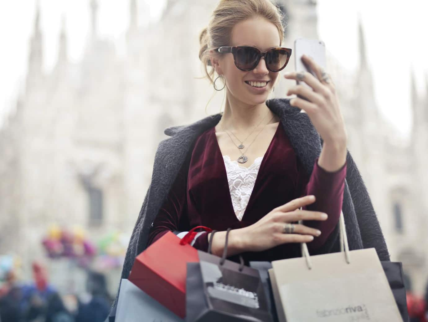 woman carrying shopping bags and looking at her phone